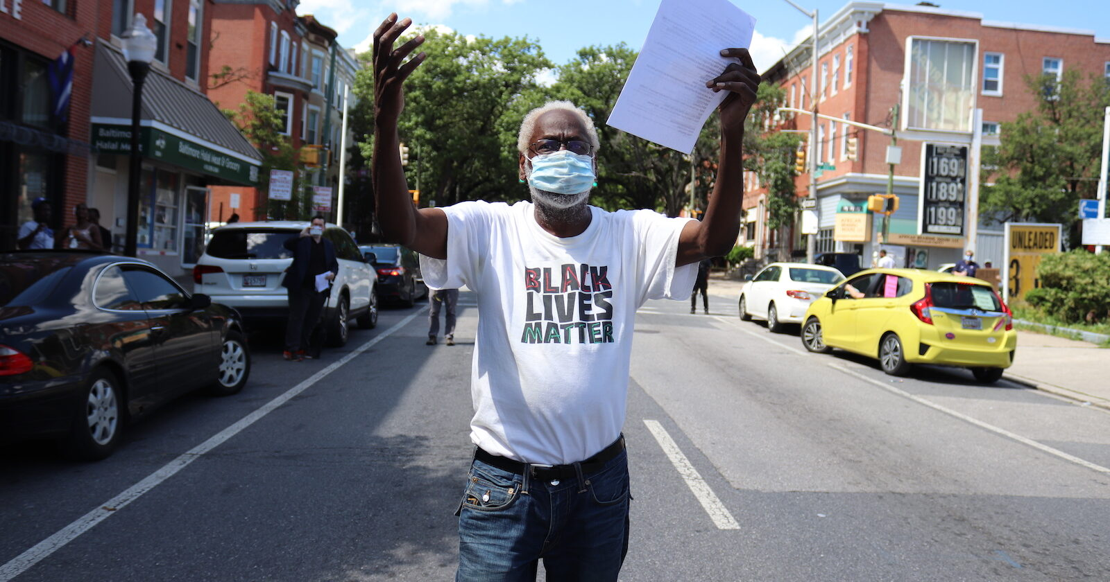 Man wearing black lives matter t-shirt walking down a street